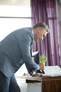 Side view of confident mature businessman reading book at desk in officeの写真素材 [FYI03657261]