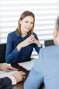 Confident young businesswoman discussing with male colleagues in board roomの写真素材 [FYI03657267]
