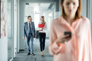 Business people walking in office corridor with female colleague using mobile phone in foregroundの写真素材 [FYI03657323]