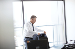 Mature businessman hanging jacket on back of office chairの写真素材 [FYI03657333]