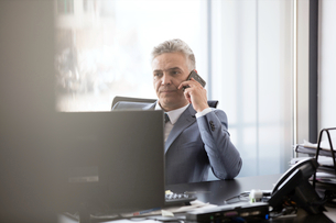 Mature businessman using mobile phone at desk in officeの写真素材 [FYI03657337]