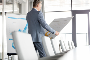 Mature businessman analyzing graph on chart in board roomの写真素材 [FYI03657342]