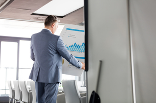 Rear view of businessman analyzing graph on chart in board roomの写真素材 [FYI03657343]