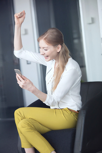 Smiling young businesswoman cheering while holding mobile phone on chair in officeの写真素材 [FYI03657346]