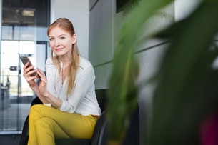 Portrait of smiling young businesswoman using mobile phone on chair in officeの写真素材 [FYI03657349]