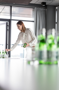 Young businesswoman arranging bottles on table in board roomの写真素材 [FYI03657396]