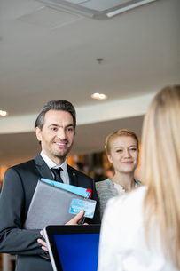 Smiling business people looking at receptionist in convention centerの写真素材 [FYI03657419]