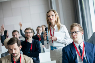 Confident businesswoman holding microphone while asking questions during seminarの写真素材 [FYI03657431]