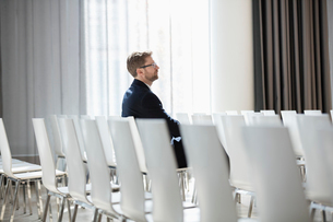 Side view of businessman sitting in seminar hallの写真素材 [FYI03657461]