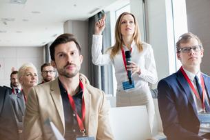 Confident businesswoman asking questions during seminarの写真素材 [FYI03657469]