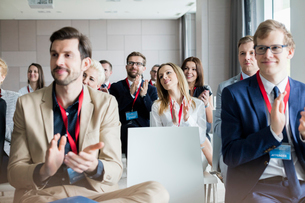 Confident business people applauding during seminarの写真素材 [FYI03657470]