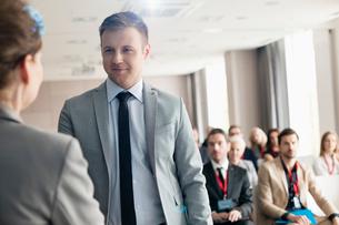 Confident businessman looking at public speaker during seminarの写真素材 [FYI03657472]
