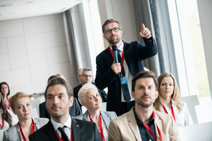 Businessman gesturing while asking question during seminar in convention centerの写真素材 [FYI03657541]