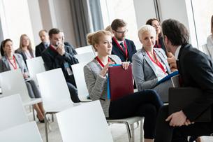 Businessman talking to businesswomen in seminar hallの写真素材 [FYI03657548]