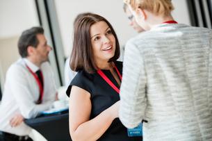 Businesswomen talking during coffee break at convention centerの写真素材 [FYI03657559]