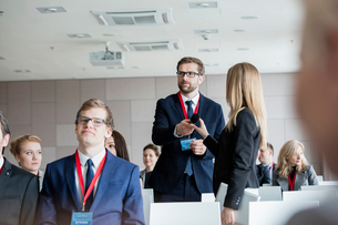 Business people holding microphone while standing during seminarの写真素材 [FYI03657563]
