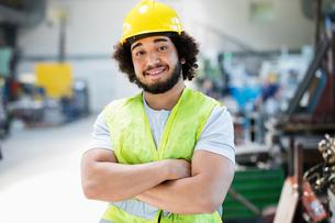 Portrait of smiling male manual worker standing arms crossed in industryの写真素材 [FYI03657608]