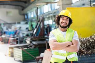 Portrait of smiling male manual worker standing arms crossed in metal industryの写真素材 [FYI03657610]