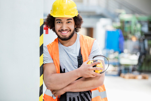 Portrait of confident male worker in protective clothing holding ear protectors at factoryの写真素材 [FYI03657620]