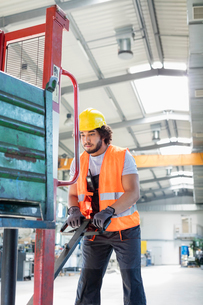 Young male worker pushing hand truck in metal industryの写真素材 [FYI03657626]