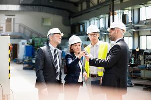 Team of business people examining machine part in metal industryの写真素材 [FYI03657633]