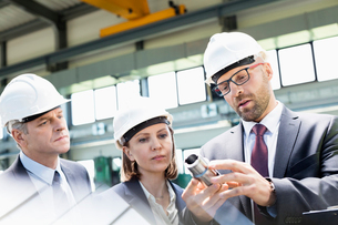Mid adult businessman explaining machine part of colleagues in metal industryの写真素材 [FYI03657635]