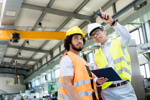 Supervisor showing something to manual worker in metal industryの写真素材 [FYI03657636]