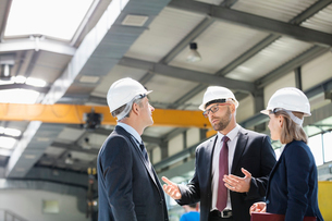 Business people wearing hardhats having discussion in metal industryの写真素材 [FYI03657639]