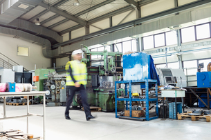 Blurred motion of male supervisor walking in metal industryの写真素材 [FYI03657641]