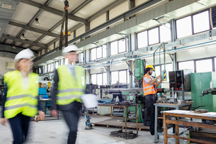 Blurred motion of business people with manual worker in background at industryの写真素材 [FYI03657646]