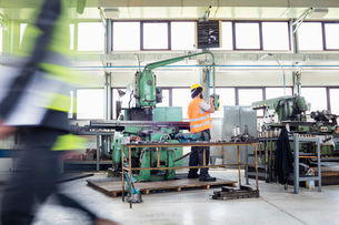 Manual worker operating machinery at metal industryの写真素材 [FYI03657648]