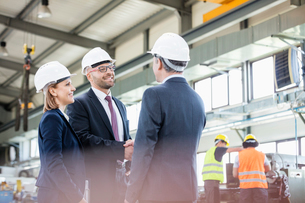 Businessmen shaking hands with workers working in background at metal industryの写真素材 [FYI03657649]