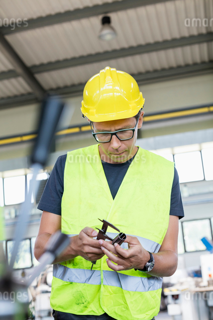 Mid adult manual worker measuring metal with caliper in industryの写真素材 [FYI03657650]