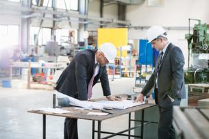 Businessmen examining blueprint at workbench in metal industryの写真素材 [FYI03657651]