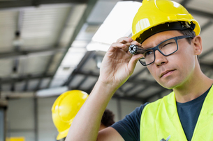 Mid adult manual worker examining metal in industryの写真素材 [FYI03657652]