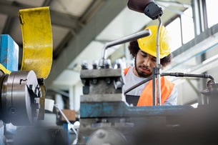 Low angle view of young manual worker working on machinery in metal industryの写真素材 [FYI03657654]