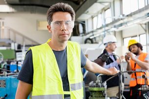 Portrait of mid adult worker wearing protective eyewear with colleagues in background at industryの写真素材 [FYI03657659]