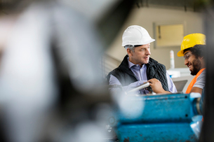 Mature male supervisor talking with worker in metal industryの写真素材 [FYI03657660]