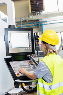 Female worker operating machinery at control panel in factoryの写真素材 [FYI03657663]