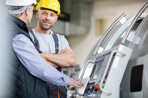 Mid adult manual worker having discussion with colleague by machinery in industryの写真素材 [FYI03657664]