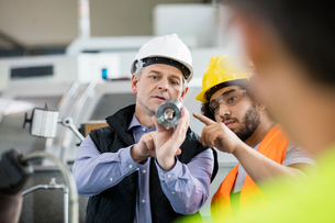 Supervisor and manual worker discussing over metal in industryの写真素材 [FYI03657665]