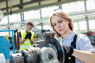 Mature female worker working on machinery with colleague in background at industryの写真素材 [FYI03657669]