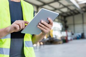 Midsection of manual worker using digital tablet in metal industryの写真素材 [FYI03657677]