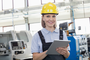 Portrait of smiling female worker using digital tablet in manufacturing industryの写真素材 [FYI03657679]
