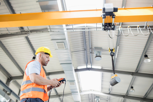 Low angle view of manual worker operating crane lifting steel in industryの写真素材 [FYI03657680]