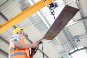Low angle view of manual worker operating crane lifting sheet metal in industryの写真素材 [FYI03657681]