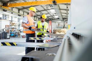 Male manual workers examining sheet metal at industryの写真素材 [FYI03657687]