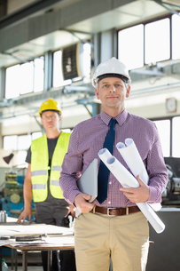 Portrait of confident male architect holding blueprints and laptop with worker in background at induの写真素材 [FYI03657697]