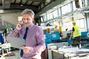 Mature male supervisor looking at clipboard while talking on mobile phone in industryの写真素材 [FYI03657702]