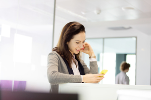 Young businesswoman using mobile phone in officeの写真素材 [FYI03657706]